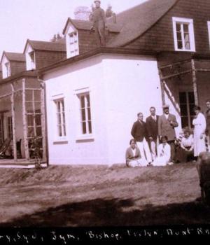 Photographie en noir et blanc d'un groupe d'estivants devant une résidence d'été blanche au toit percé de plusieurs lucarnes.