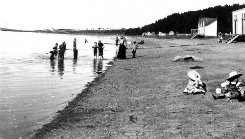 Des femmes et des enfants profitent de la plage. Deux enfants jouent dans le sable. Les baigneurs portent des maillots longs.