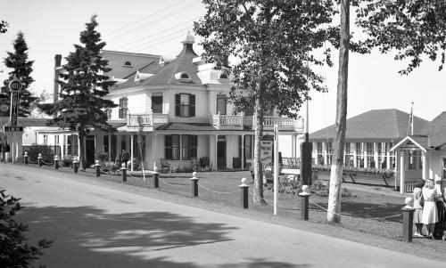 black and white photograph of an inn and a pavilion with many windows.