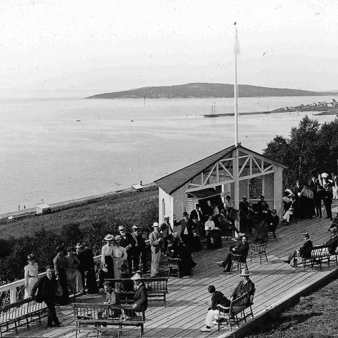Vacationers conversing on a wood terrace built on a cliff overlooking the water.