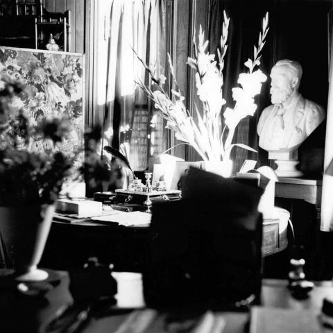 Photographie en noir et blanc d'un bureau à la décoration chargée de bibelots et de fleurs.