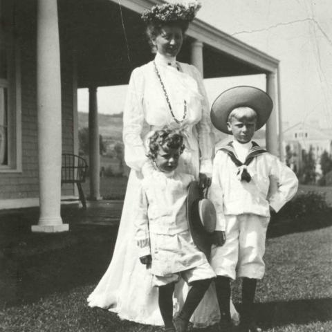Une femme en robe blanche très élégante pose avec ses deux enfants près d'une maison.
