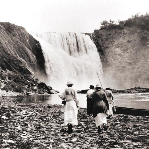 Four women walking at the foot of a waterfall, heading toward a guide standing in a canoe.