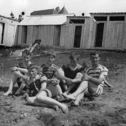 Five adolescents wearing old-fashioned bathing suits and sitting in the sand near a row of bathing cabins.