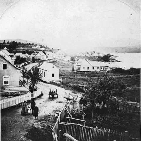 Photographie ancienne d'un village vallonné en bord de mer. Quelques individus sont dans la rue, près d'un cheval attelé.