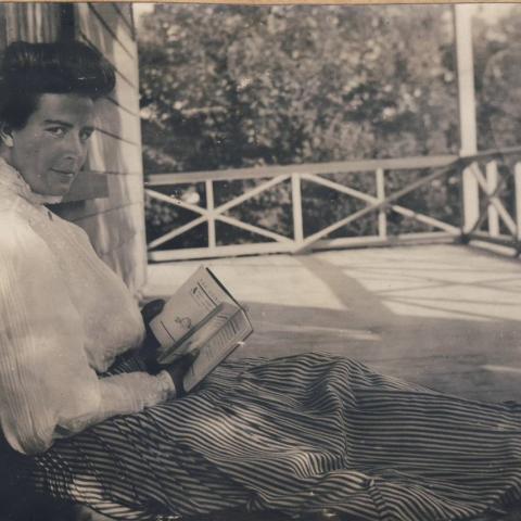 Une femme lit, assise par terre, sur une grande galerie, le dos appuyé au mur de la maison.