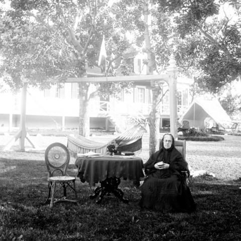 Une vieille femme lit, assise sur une chaise disposée sur le gazon.