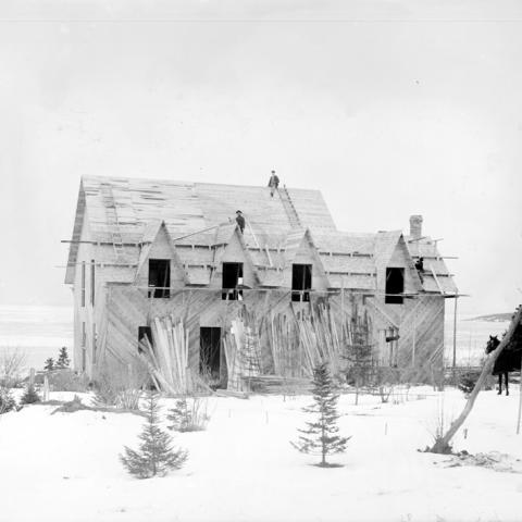 Des ouvriers se trouvent sur le toit d'une maison en construction en plein hiver.