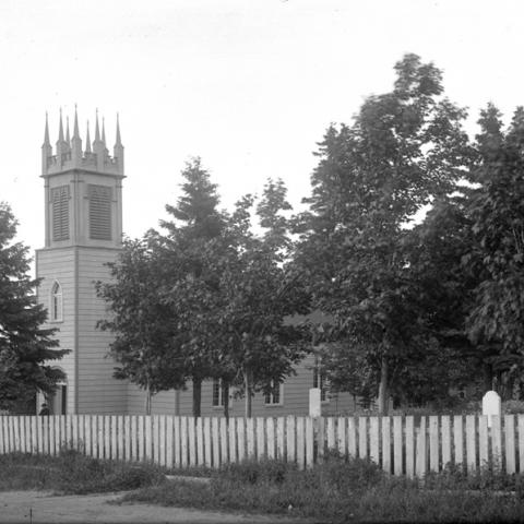 View of a small church with a neo-Gothic bell tower and connected cemetery. The lot is fenced.