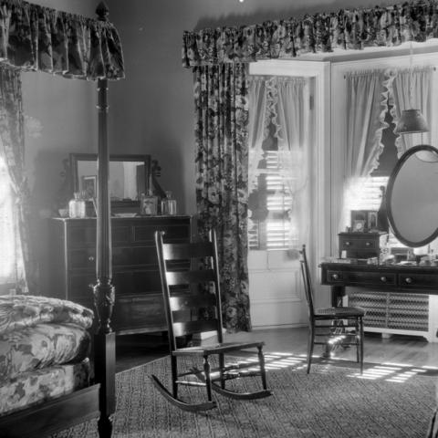 A dressing table and a canopy bed in a bedroom decorated with flowery drapes.