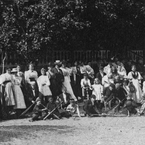 Photographie de groupe devant une grande galerie, où des enfants exposent plusieurs pièces d'équipement sportif.