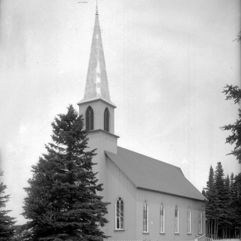 A small church in a wooded area.