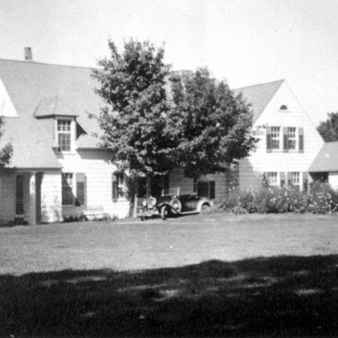 A villa and its surrounding land. An old car parked in front of the house.