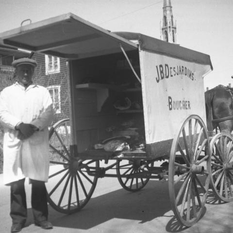 Un boucher portant un vêtement de travail blanc pose devant sa voiture de livraison à quatre roues, tirée par un cheval.