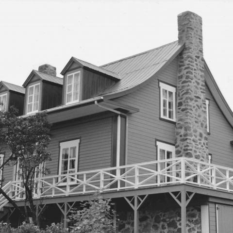 An old but solid Canadienne with stone chimney, metal roof and horizontal-plank walls.
