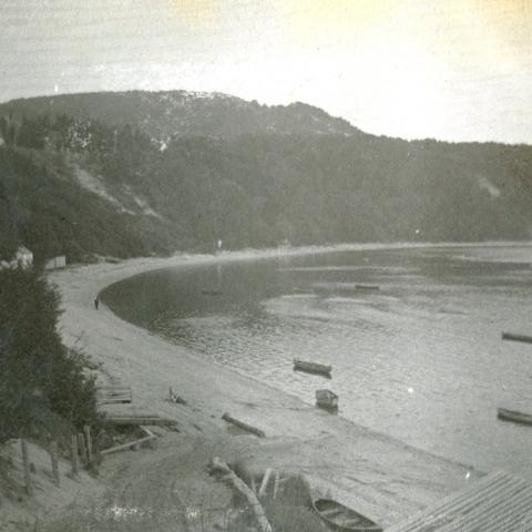 Au pied d'une falaise se trouvent une plage et une anse où flottent quelques canots.