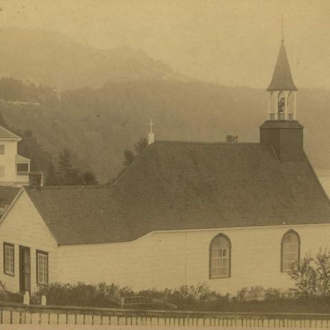 Une chapelle et une grande maison blanche situées en haut d'une falaise font face au fleuve.