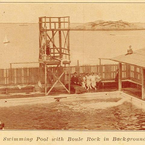 Many people sitting around a fenced pool with a large diving platform.