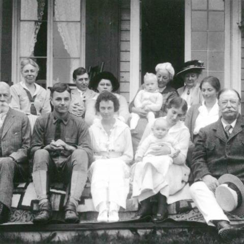Douze personnes de tout âge posent pour une photographie de famille sur le perron d'une résidence.