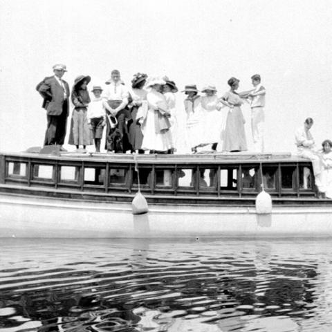 A dozen people posing on the roof of a motorized yacht.