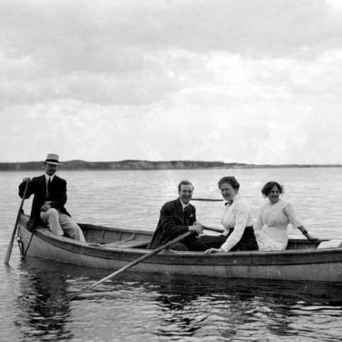 A small group in a rowboat, on the water.