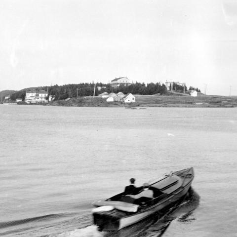 Un homme dans un petit bateau se dirige vers la Pointe.
