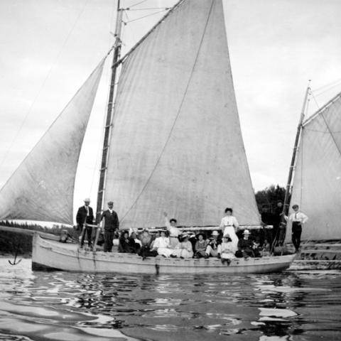 A sailboat floating on the water, filled with passengers.