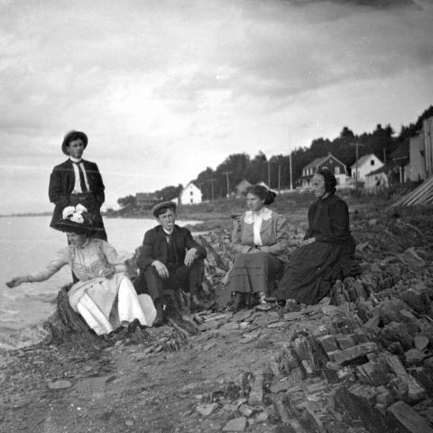 Cinq adultes, dont une dame âgée, posent sur une plage très rocheuse. Une femme semble lancer du pain à un oiseau hors champ.