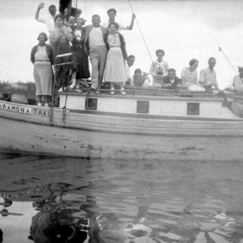 Simply dressed people aboard a small boat.