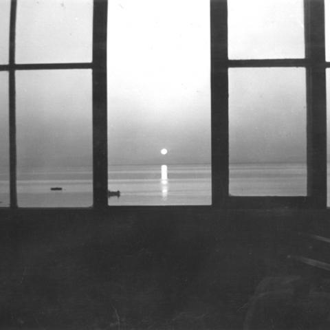Une vieille dame assise à la fenêtre regarde le soleil se coucher sur le fleuve Saint-Laurent.