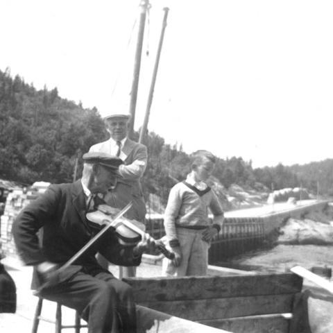 Un vieil homme joue du violon sur un quai.