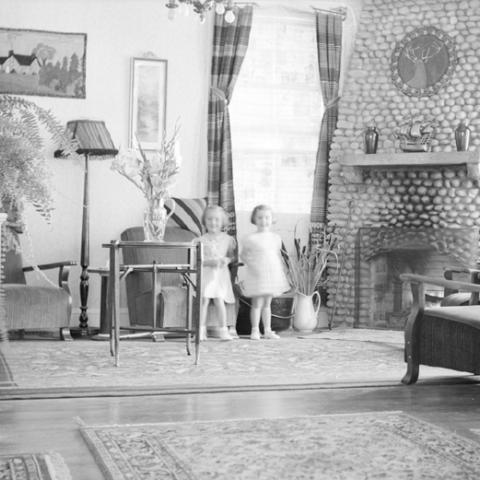 Deux petites filles en robe blanche posent dans le salon d'un hôtel.