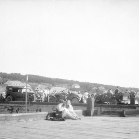 Two young women talking on an action-filled wharf, with several cars parked in the background.