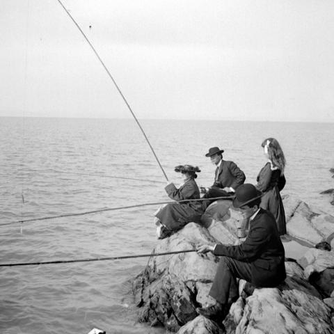 Two men and two women fishing from rocks.