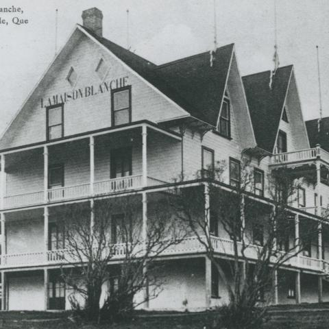 A large building with wood siding, surrounded by verandas and dormer windows.