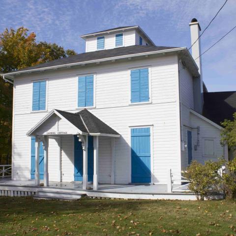 Grande maison blanche en bois dont les volets bleus sont tous fermés.