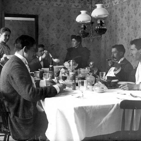 A group sitting at a well-garnished table, with a woman serving the meal.
