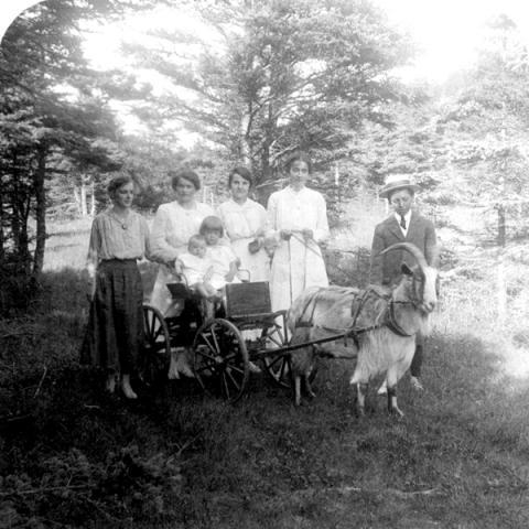 Portrait de famille avec deux enfants assis dans une petite carriole tirée par une chèvre.
