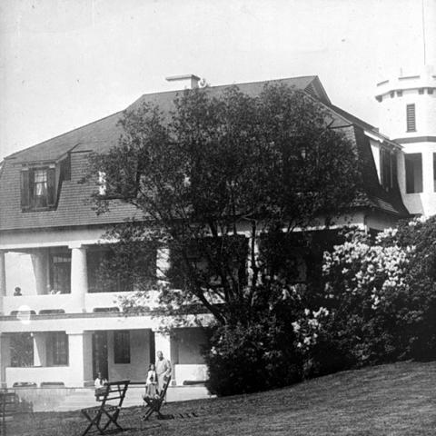 Une grande maison, bordée de grandes galeries à deux étages, est dotée d'une tourelle à créneaux.