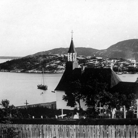A chapel and its cemetery overlooking a bay where boats, including two sailboats, are anchored.