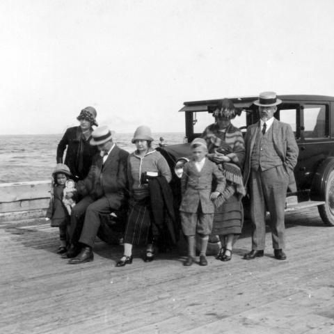 Cinq adultes et deux enfants en vacances posent devant une automobile ancienne stationnée sur un quai.