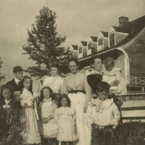 Three women and several children posing in front of a large old house with cedar shingling.