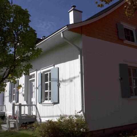 Photographie en couleurs d'une maison ancienne blanche aux volets bleu pâle, entourée de verdure.