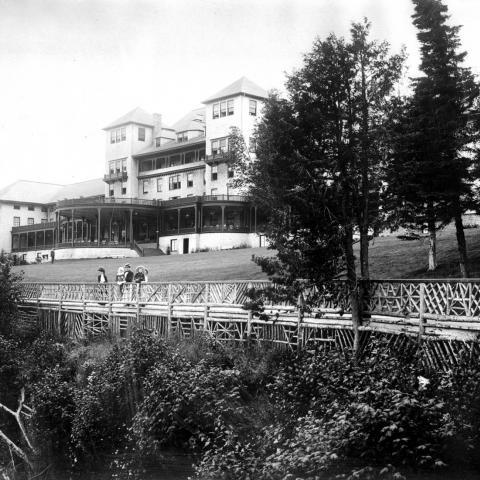 Un grand hôtel doté de grandes galeries. Des dames et de jeunes enfants observent le paysage près d'une balustrade.