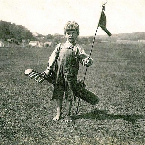 Un enfant caddie, sac de golf à l'épaule, tient un drapeau. Il est pieds nus.