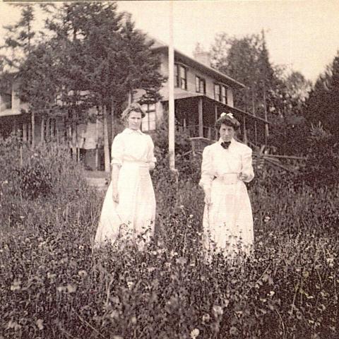 Deux jeunes femmes en robe posent dans un champ, près d'une maison, tenant chacune un contenant blanc.
