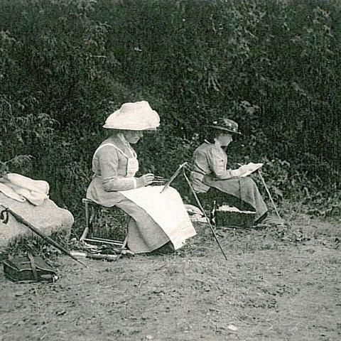 Deux femmes peignent sur le bord d'une plage, leurs toiles appuyées sur des chevalets portatifs.